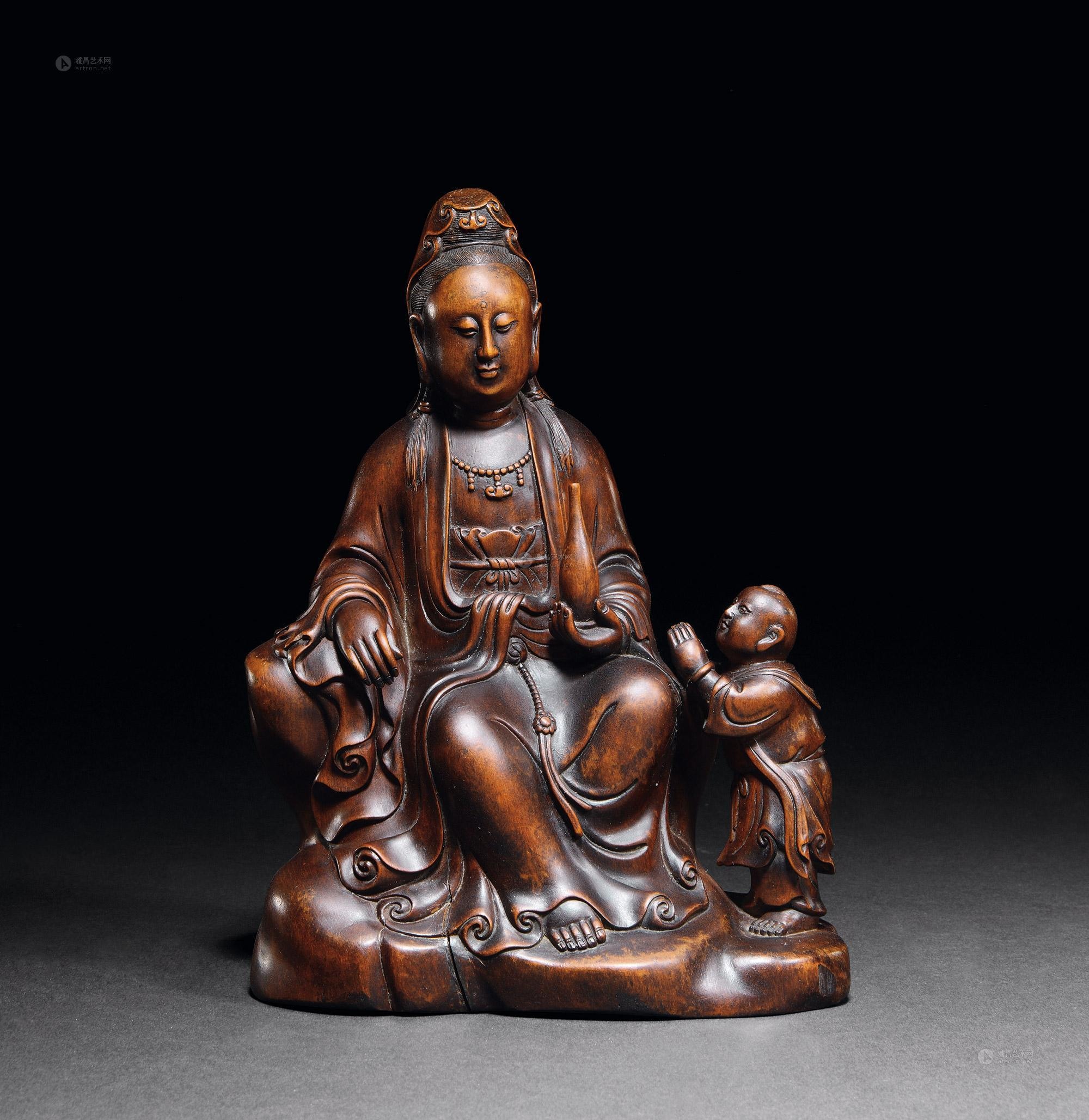 童子拜观音的题材出自《华严经.入法界品》,经中提到善财童子,每次参见善知识和菩萨时都会双手合十,顶礼膜拜。明清时期寺院多奉观音,其观音殿的寺壁常常绘塑跟观音菩萨有关的事迹与传说,其中童子拜观音则是必不可少的。 此尊童子拜观音是典型的明末清初中原风格造型。以黄杨木雕琢而成,木质古朴,色泽文雅,质地细腻,雕刻制品精致圆润。常见的观音菩萨都是亭亭玉立的女性形象,眼前这尊观音菩萨稍有不同,略呈男相。佛经中称其为善男子等等,法力无边,可无量幻化身形,岂只男女。所雕观音法相庄严,大耳垂肩,虽现男相,却同样面容圆润,